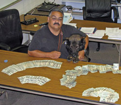 Officer and K-9 unit seated beside a table topped with money.